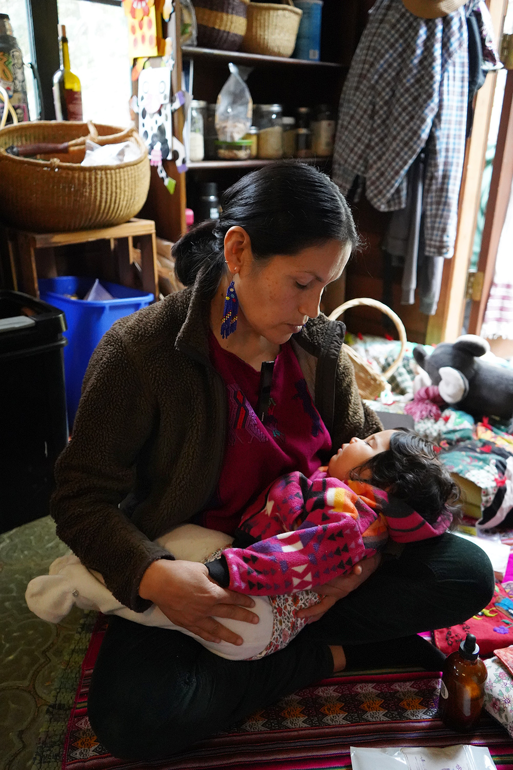Midwife Maria Ramos Bracamotes cradles her baby at her home.